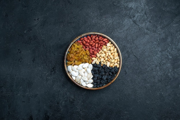 Top view hazelnuts and raisins and other nuts on dark grey background nut snack dry fruit photo