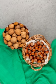 Top view hazelnuts and walnuts whole inside basket on the grey
