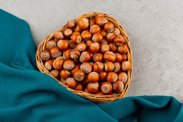 Top view hazelnuts whole brown inside basket on the grey floor