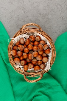 Top view hazelnuts whole inside basket on the grey background