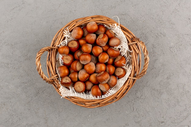 Top view hazelnuts whole inside basket on the grey floor