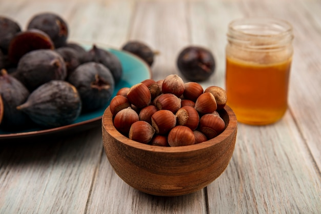 Top view of hazelnuts on a wooden bowl with ripe black mission figs on a blue dish with honey in a glass jar on a grey wooden wall
