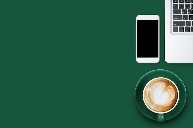 Top view or over head of latte coffee or cappuccino coffee with smart phone and laptop on green table with copy space