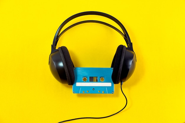 Top view of headphone and blue classic tape cassette against yellow isolated background