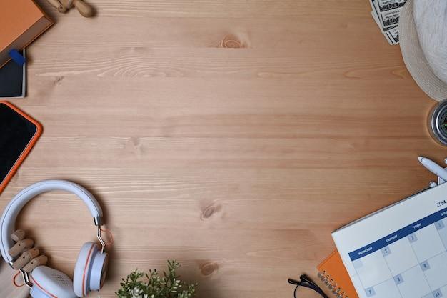 Наушники, мобильный телефон, календарь и тетрадь вида сверху на деревянном фоне.