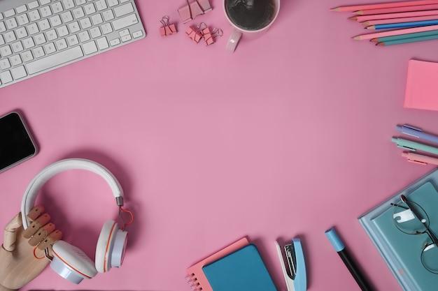 ピンクの背景にトップビューのヘッドフォン、ノートブック、文房具、スマートフォン。