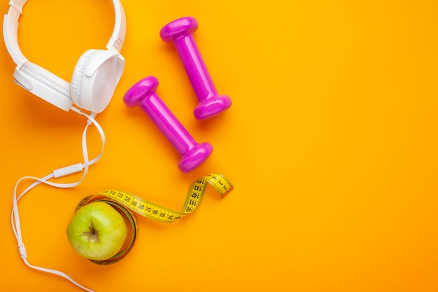 Top view headphones and apple on yellow background