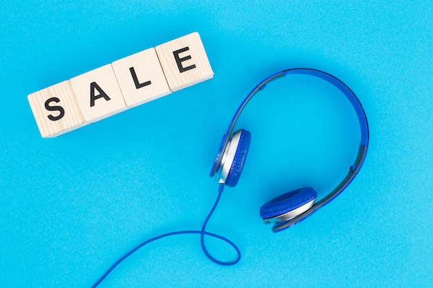 Top view of headphones and sale lettering isolated on blue