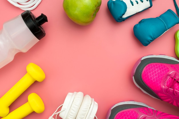 Vista dall'alto di cuffie con pesi ed elementi sportivi essenziali