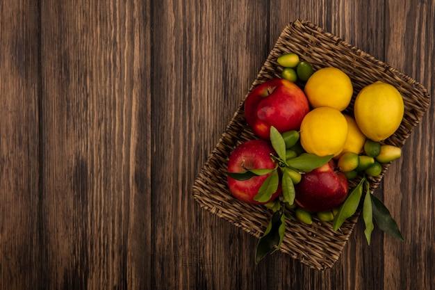 Vista dall'alto di frutti salutari come mele, limoni e kinkan su un vassoio di vimini su una parete in legno con spazio di copia