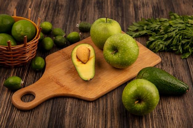 Vista dall'alto di mele sane su una tavola da cucina in legno con limette su un secchio con avocado feijoas e prezzemolo isolato su una superficie in legno
