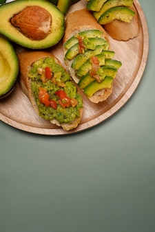 Top view healthy avocado toasts on wooden plate.