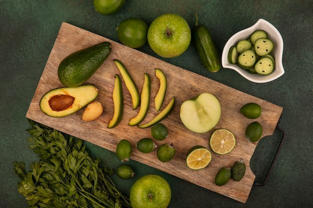 Vista dall'alto di avocado sano con fette su una tavola di cucina in legno con mezze lime di feijoas con fette di cetriolo tritate su una ciotola con mele verdi di lime e prezzemolo isolato su uno sfondo verde