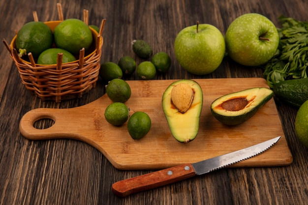 Vista dall'alto di avocado sani su una tavola da cucina in legno con coltello con lime su un secchio con mele feijoas e prezzemolo isolato su uno sfondo di legno