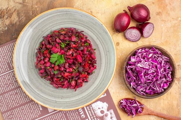 Insalata di barbabietola sana vista dall'alto su un piatto grigio con cipolle rosse e cavolo tritato in una ciotola su un tavolo di legno