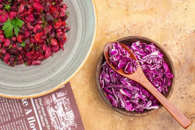 パセリの束とテキスト用の小さなスペースのある木製の背景に刻んだ赤キャベツのボウルで作られた灰色のプレート上のトップビューの健康的なビートサラダ