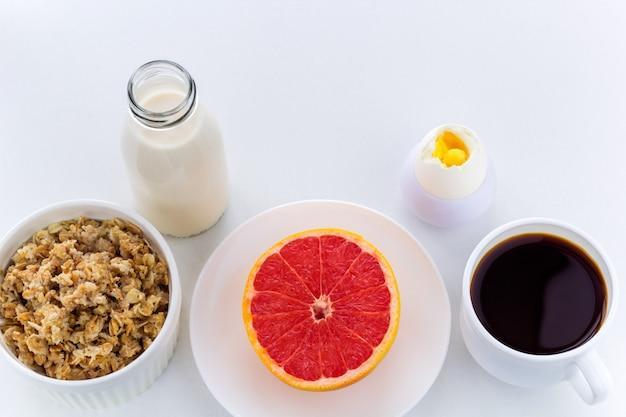 Top view healthy breakfast milk bottle, coffee, oatmeal, hard boiled egg, grapefruit