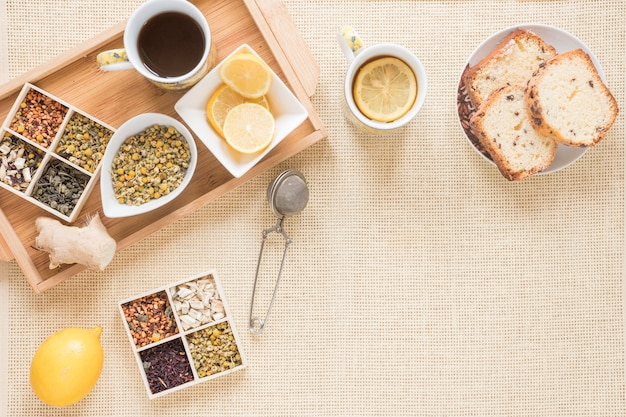 Top view of healthy breakfast with variety of herbs; lemon; strainer; bread; ginger and ingredients