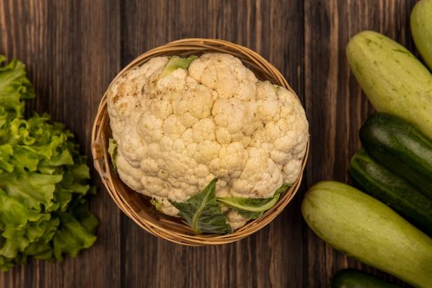Vista dall'alto di un sano cavolfiore su un secchio con verdure come cetrioli lattuga e zucchine isolate su una parete in legno