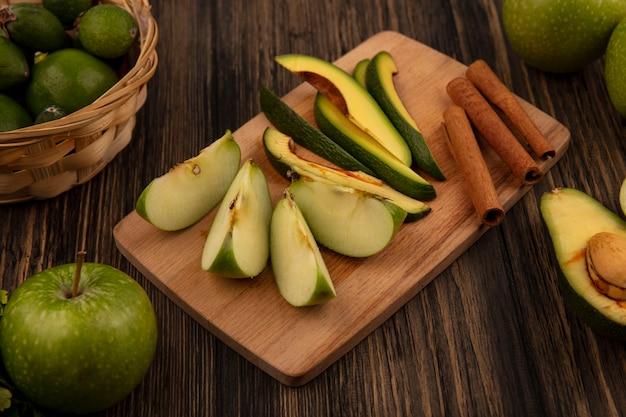 Vista dall'alto di sani fette tritate di avocado su una tavola da cucina in legno con bastoncini di cannella e fette di mela con feijoas su una superficie di legno