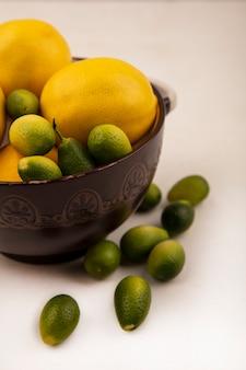 Vista dall'alto di agrumi sani come limoni e kinkan su una ciotola con kinkan isolato su una superficie bianca