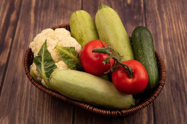 Top view of healthy and colorful vegetables such as tomatoes zucchini cucumber and cauliflower on a bucket on a wooden wall