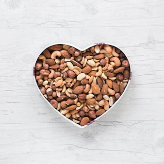 Top view of healthy dryfruits in heart shape on wooden desk
