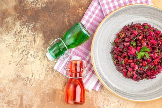 Vista dall'alto concetto di alimentazione sana con insalata su un piatto di ceramica e due bottiglie colorate di olio d'oliva nelle vicinanze su uno sfondo con spazio di copia