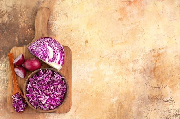 コピースペースのある木製のテーブルで野菜サラダを準備するためのまな板の上にいくつかの刻んだキャベツと赤玉ねぎを使ったトップビューの健康食品のコンセプト