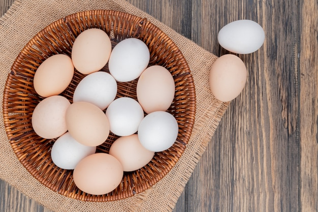 Top view of healthy and fresh chicken eggs on a bucket on sack cloth on a wooden background