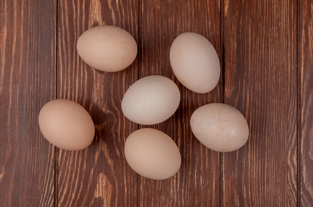 Top view of healthy and fresh eggs isolated on a wooden background