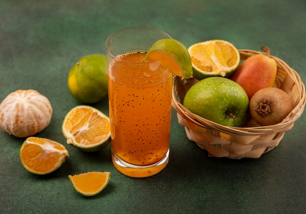 Top view of healthy and fresh fruits such as apples pear kiwi on a bucket with fresh fruit juice in a glass with tangerines isolated