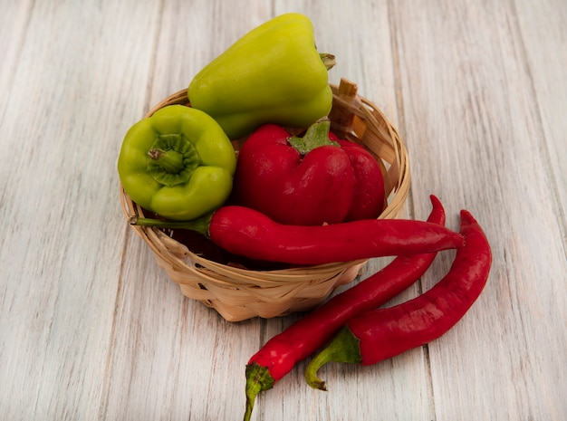 Top view of healthy and fresh peppers on a bucket with chili peppers isolated on a grey wooden background