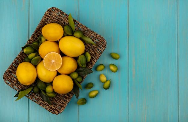 Vista dall'alto di frutti sani come kinkan e limoni su un vassoio di vimini su uno sfondo di legno blu con spazio di copia