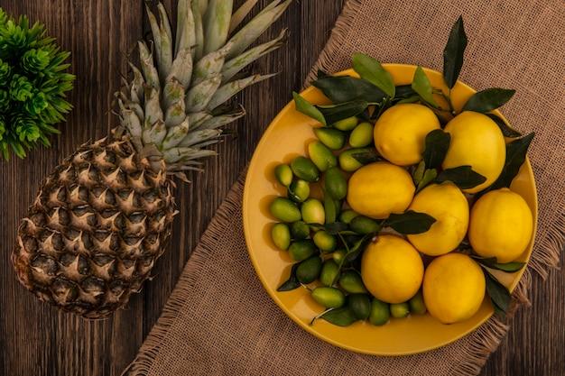 Vista dall'alto di frutti sani come limoni e kinkan su un piatto giallo su un panno di sacco con ananas isolato su una superficie in legno