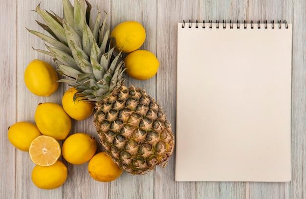 Vista dall'alto di frutti sani come ananas e limoni isolati su una parete in legno grigio con spazio di copia