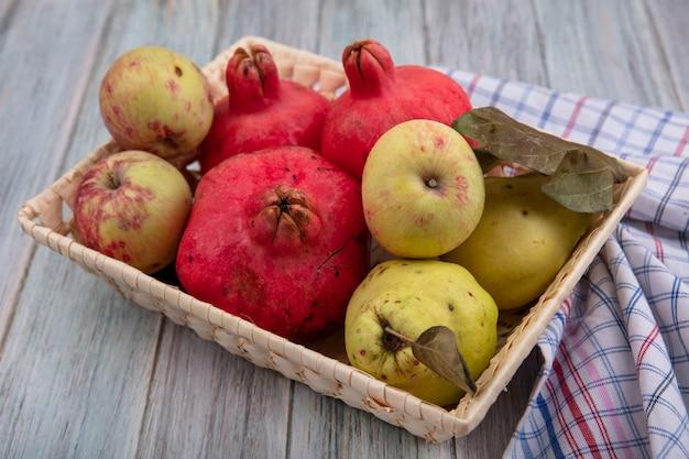 Vista dall'alto di frutti sani come melograni e mele cotogne su un secchio su un panno controllato su uno sfondo grigio