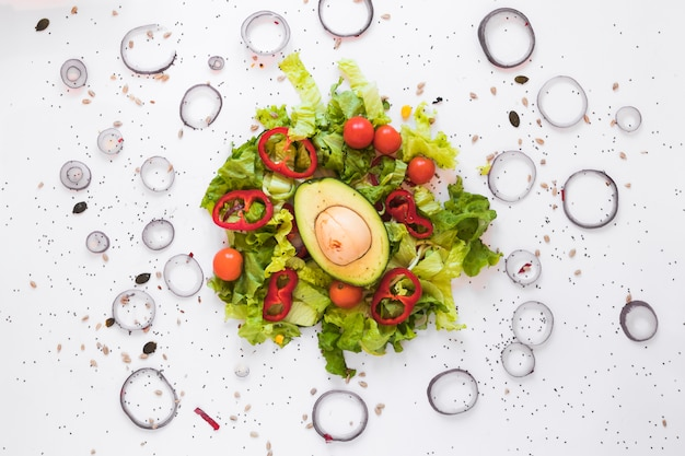 Top view of healthy garnished salad with fresh avocado and vegetables