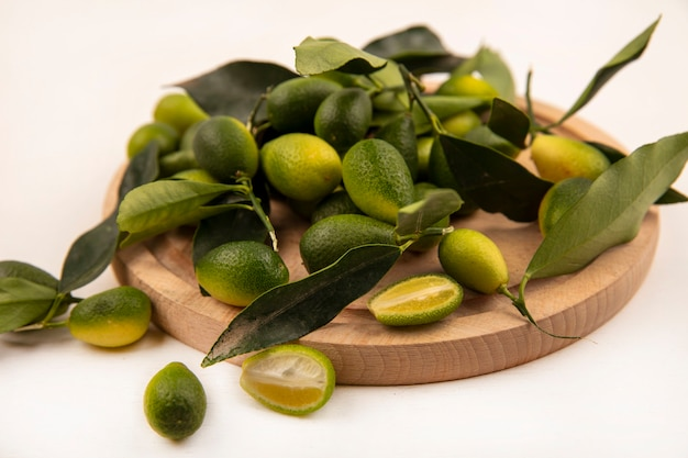 Top view of healthy kinkans with leaves isolated on a wooden kitchen board on a white wall