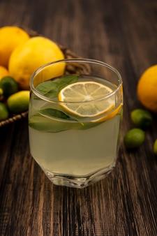 Vista dall'alto di un sano succo di limone con limoni e kinkan su un vassoio di vimini su una superficie di legno