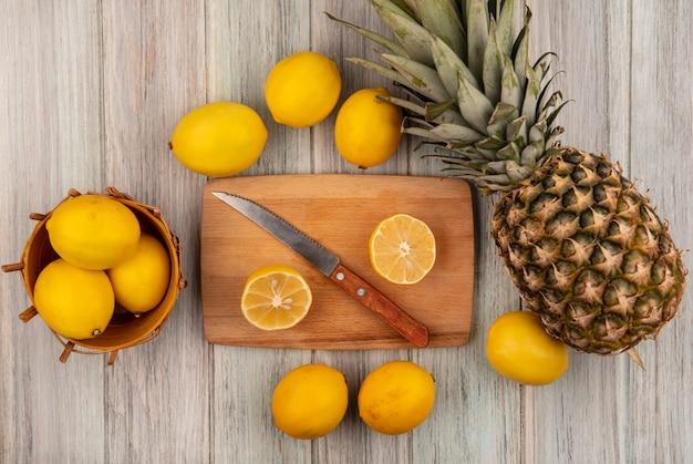 Vista dall'alto di limoni sani su un secchio con mezzi limoni su una tavola da cucina in legno con coltello con limoni e ananas isolato su uno sfondo di legno grigio