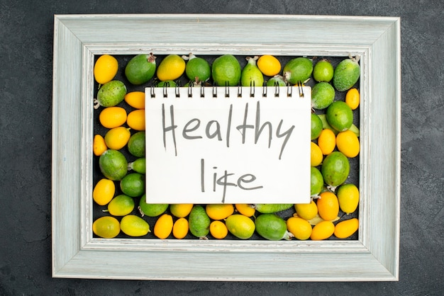 Top view of healthy life writing on spiral notebook on collection of citrus fruits on picture frame on dark background