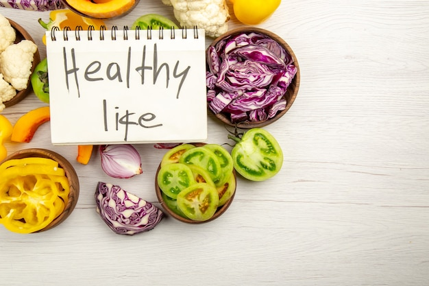 Top view healthy life written on notebook cut green tomatoes cut red cabbage cut pumpkin cauliflower cut bell peppers in bowls on white wooden surface free space