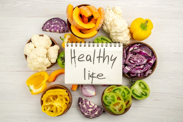 Top view healthy life written on notebook cut green tomatoes cut red cabbage cut pumpkin cauliflower cut bell peppers in bowls on wooden surface