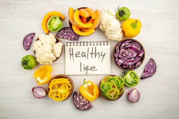 Top view healthy life written on notebook red cabbage cauliflower yellow bell pepper green tomato in bowls on surface