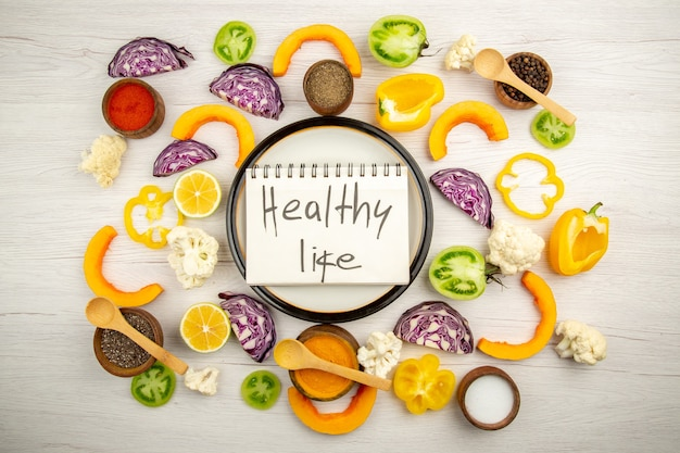 Top view healthy life written on notebook on round plate cut vegetables different spices in small bowls on white surface