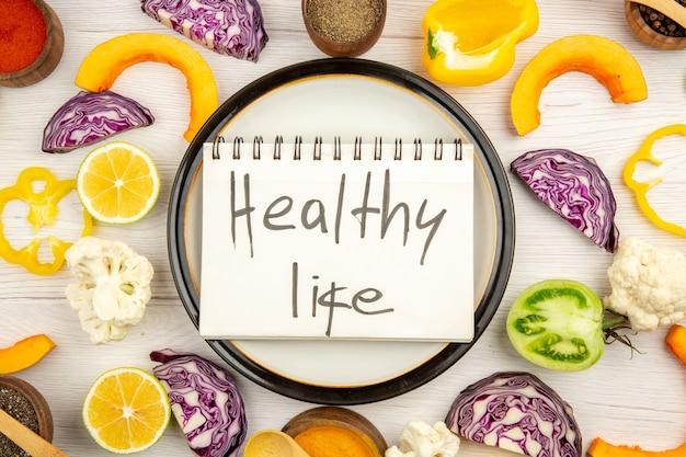 Vista dall'alto vita sana scritta sul taccuino sul piatto rotondo tagliare le verdure diverse spezie in piccole ciotole su bianco superficie di legno