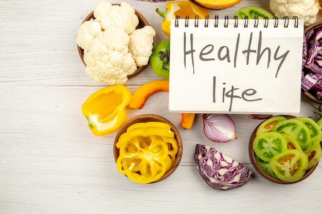 Top view healthy life written on notepad cut green tomatoes cut red cabbage cut pumpkin cauliflower cut bell peppers in bowls on wooden surface