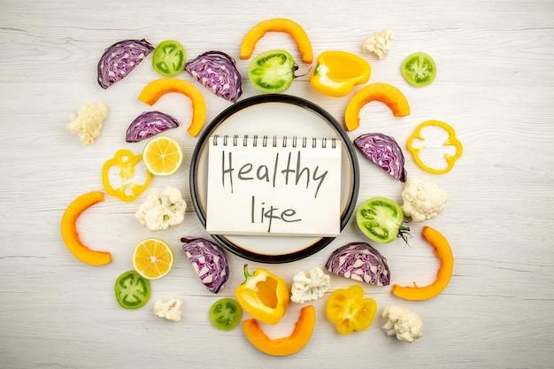 白い木の表面の丸い大皿カット野菜のメモ帳に書かれた上面図健康的な生活