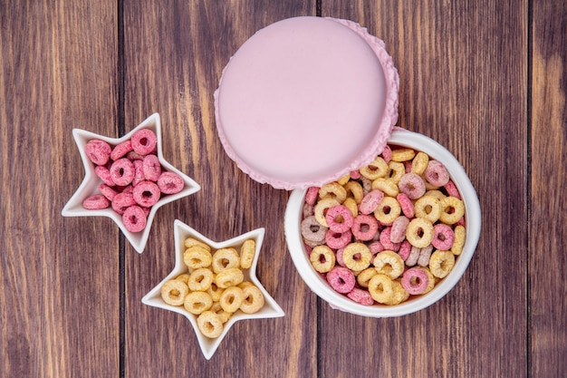 Top view of healthy and loop cereals on a circle white bowl and star shaped bowls on wooden surface